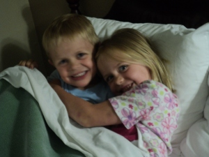 The two oldest watching a movie in bed.